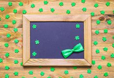St Patricks Day holiday background with green quatrefoils and frame with green bow tie on the wooden background royalty free stock photography