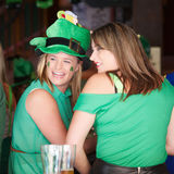 St Patricks Day girls. Candid portrait of two attractive girls sitting in an Irish pub on Saint Patricks day and dressed in green to celebrate; Brisbane, 15 Stock Photo