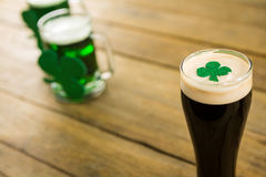St Patricks Day glass of beer with shamrock. On wooden surface Stock Image