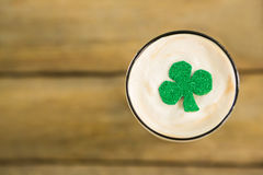 St Patricks Day glass of beer with shamrock. On wooden surface Royalty Free Stock Photo