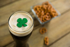 St Patricks Day glass of beer with shamrock. On wooden surface Stock Images