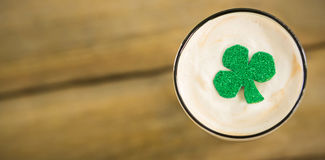 St Patricks Day glass of beer with shamrock. On wooden table Stock Photography