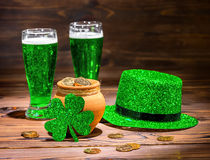 St Patricks day with glasses of green beer, leaf clover, leprechaun hat and pot full gold coins on vintage wooden. Background, close up stock image