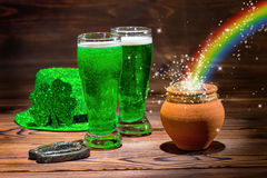 St Patricks day with glasses of green beer, shamrock, leprechaun. Hat, horseshoe, pot full gold coins and rainbow on vintage wooden background, close up Royalty Free Stock Images