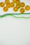 St Patricks Day gold chocolate coin and beads Royalty Free Stock Image