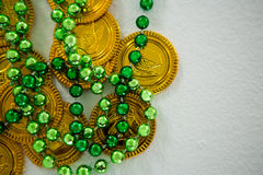 St Patricks Day gold chocolate coin and beads Royalty Free Stock Photos