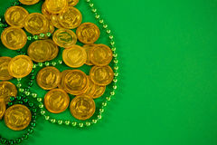 St Patricks Day gold chocolate coins and beads Royalty Free Stock Photos