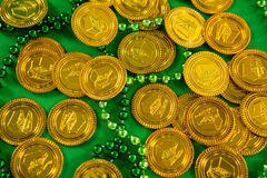 St Patricks Day gold chocolate coins and beads Stock Photography