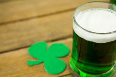 St Patricks Day green beer with shamrock. On wooden surface Stock Images