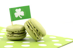St Patricks Day green macaron cookies. Happy St Patricks Day green macaron cookies with shamrock flag on white table Royalty Free Stock Images