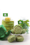 St Patricks Day green party food. St Patricks Day party food green macarons, candy jar and stack of green pancakes with shamrock flags and leprechaun hat on Royalty Free Stock Photography