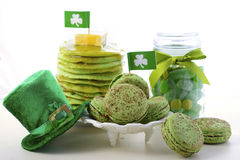 St Patricks Day green party food. St Patricks Day party food green macarons, candy jar and stack of green pancakes with shamrock flags and leprechaun hat on Royalty Free Stock Photo