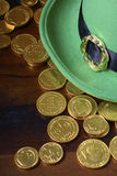 St Patricks Day hat and gold coins. Happy St Patricks Day green leprechaun hat with gold covered chocolate coins on dark wood background Royalty Free Stock Images