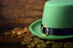 St Patricks Day hat and gold coins. Happy St Patricks Day green leprechaun hat with gold covered chocolate coins on dark wood background Royalty Free Stock Photo