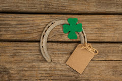 St Patricks Day horseshoe with empty tag and shamrock on wooden table Royalty Free Stock Photography