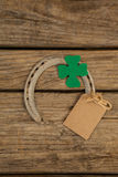 St Patricks Day horseshoe with empty tag and shamrock on wooden table Stock Photos