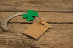 St Patricks Day horseshoe with empty tag and shamrock on wooden table Stock Photo