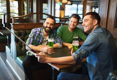 Friends taking selfie with green beer at pub Stock Images