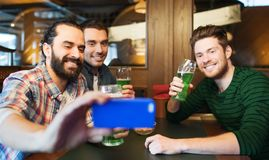 Friends taking selfie with green beer at pub Stock Photography