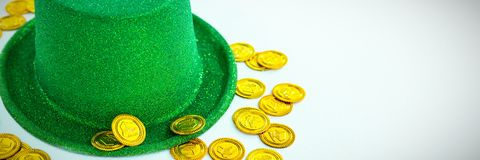 St. Patricks Day leprechaun hat and chocolate gold coins. On white background Stock Images