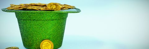 St Patricks Day leprechaun hat filled with chocolate gold coins. On white background Royalty Free Stock Image