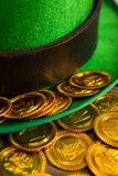St Patricks Day leprechaun hat with gold chocolate coins. St Patricks Day close-up of leprechaun hat with gold chocolate coins Stock Photos