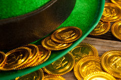 St Patricks Day leprechaun hat with gold chocolate coins. on wooden background Royalty Free Stock Photography