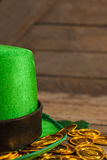 St Patricks Day leprechaun hat with gold chocolate coins. on wooden background Stock Photo