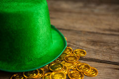 St Patricks Day leprechaun hat with gold chocolate coins. on wooden background Stock Image