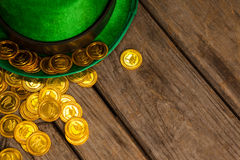 St Patricks Day leprechaun hat with gold chocolate coins. on wooden background Royalty Free Stock Image