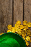 St Patricks Day leprechaun hat with gold chocolate coins. on wooden background Stock Photos
