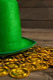 St Patricks Day leprechaun hat with gold chocolate coins. on wooden background Royalty Free Stock Images