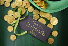 St Patricks Day leprechaun hat with gold chocolate coins. Happy St Patricks Day leprechaun hat with gold chocolate coins on vintage style green wood background Stock Photos