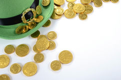 St Patricks Day leprechaun hat with gold chocolate coins. Happy St Patricks Day leprechaun hat gold chocolate coins on white table Stock Images