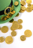 St Patricks Day leprechaun hat with gold chocolate coins. Happy St Patricks Day leprechaun hat with gold chocolate coins on white table Royalty Free Stock Image