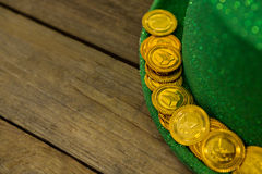 St Patricks Day leprechaun hat with gold chocolate gold coins. on wooden background Royalty Free Stock Photo