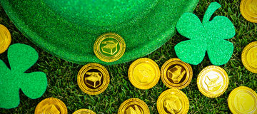 St Patricks Day leprechaun hat shamrocks and chocolate gold coins. On grass Stock Photo