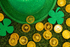 St. Patricks Day leprechaun hat, shamrocks and chocolate gold coins. On grass Stock Image
