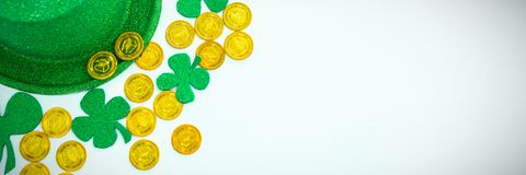 St. Patricks Day leprechaun hat, shamrocks and chocolate gold coins. On white background Stock Images