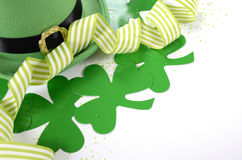 St Patricks Day leprechaun hat with shamrocks. Happy St Patricks Day leprechaun hat with shamrocks and party ribbons on white table Stock Image
