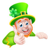 St Patricks Day Leprechaun Illustration. Leprechaun cartoon character peeking above a sign and giving a thumbs up Royalty Free Stock Images