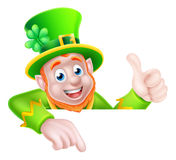 St Patricks Day Leprechaun Pointing. Leprechaun cartoon St Patricks Day character peeking above a sign pointing down at it and giving a thumbs up Royalty Free Stock Images