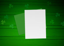 St. Patricks day mock up scene with envelope, blank paper, wooden background and clover leaves Stock Photo
