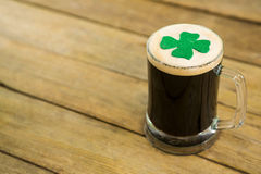 St Patricks Day mug of beer with shamrock. On wooden surface Stock Images