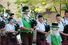 St Patricks Day Parade. Bagpipes band during the Saint Patricks day parade, Brisbane, 15 March 2014; one man wear the Leprechaun costume Stock Image