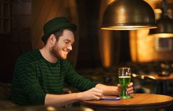 Man with smartphone and green beer at bar or pub. St patricks day, people and technology concept - happy man with smartphone drinking green beer and reading Royalty Free Stock Photos