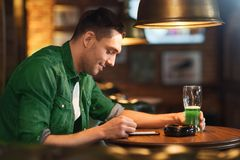 Man with smartphone and green beer texting at bar. St patricks day, people and technology concept - happy man with smartphone drinking green beer and reading Royalty Free Stock Photos