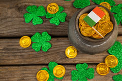 St. Patricks Day pot of chocolate gold coins with irish flag and shamrocks. On wooden table royalty free stock photo