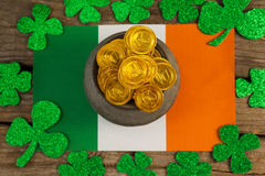 St. Patricks Day pot of chocolate gold coins and irish flag surrounded by shamrock. On wooden table royalty free stock photo