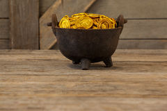 St. Patricks Day pot filled with chocolate gold coins. On wooden background Royalty Free Stock Photography